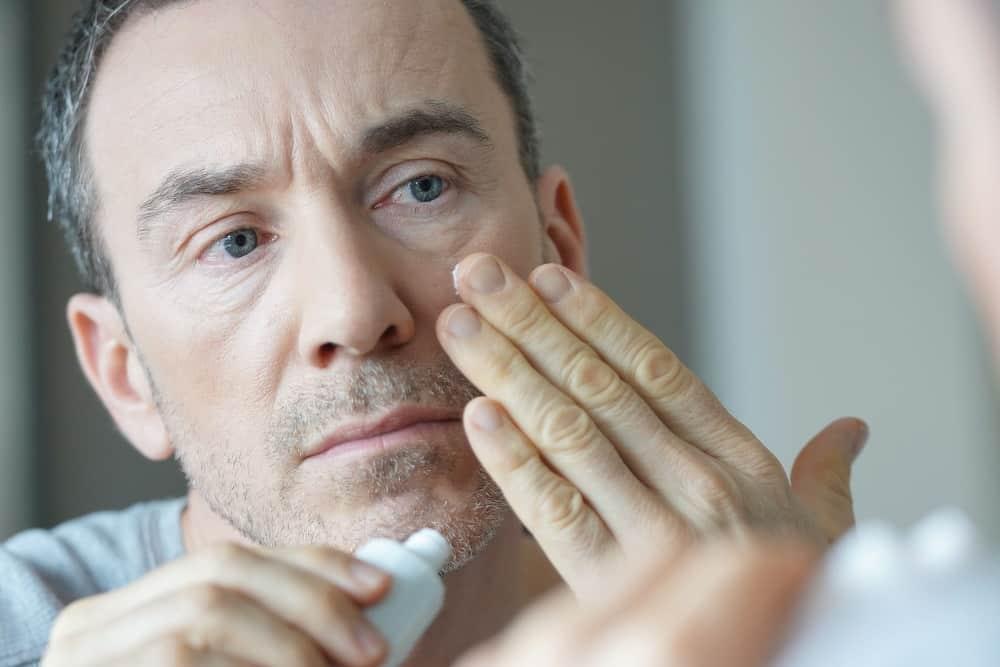 Portrait of man applying cream